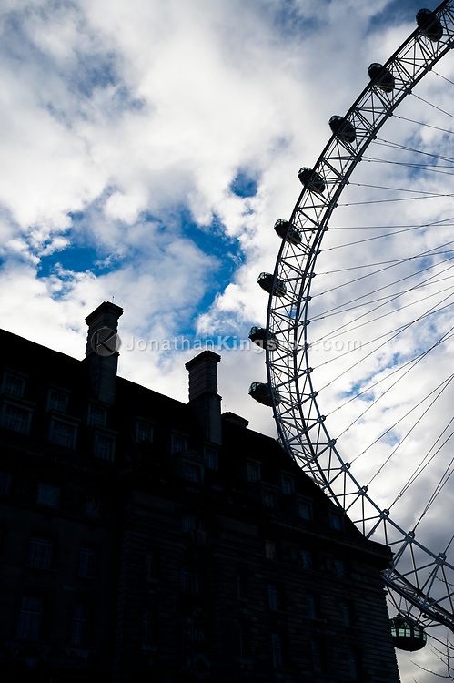 Low angle, silhouetted view of the London Eye, also known as the Millennium Wheel, and the County Hall building in London, England.