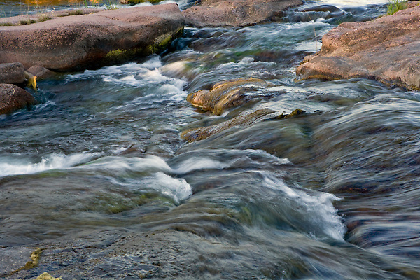 Stock photo of water flowing between rock formations in the Llano River in the Texas Hill Country