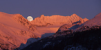 Full moon rises over Mt. Weart and the Armchair Glacier, with pink alpenglow on the mountain. Whistler, BC Canada.