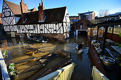 © Licensed to London News Pictures. 27/12/2015. York, UK.  A worker at the Red Lion pub in central York moves beer barrels displaced during heavy flooding in the city. Large areas of the North of England have been hit by severe flooding following unusually heavy rainfall in December. Photo credit: Ben Cawthra/LNP