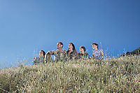 Parents with three children (7-12) sitting on hill looking at view