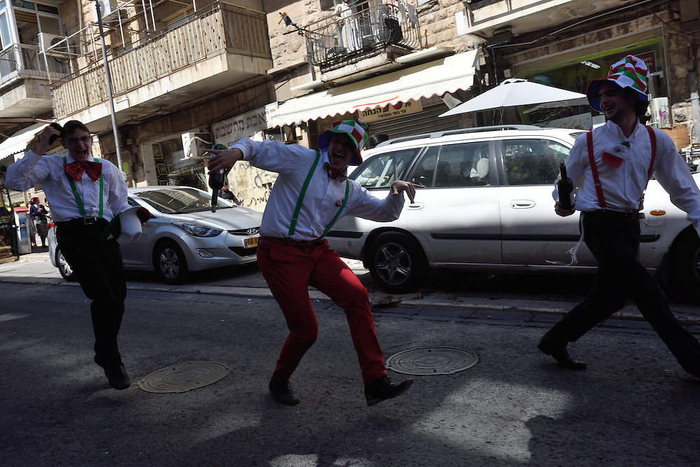 Utra-Orthodox Jewish men, waaering costumes, dance in the street during celebrations of Purim Holiday in the Ultra-Orthodox Jewish neighbourhood of Mea Shearim in Jerusalem, on March 6, 2015. The Jewish holiday of Purim commemorates the salvation of the Jews living with in the borders of the ancient Persian Empire. Purim customs include food gifts, charity, wearing costumes and drinking heavily.