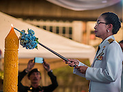 12 AUGUST 2015 - BANGKOK, THAILAND: A Thai civil servant lights a ceremonial candle during a program to honor Queen Sirikit of Thailand on her 83rd birthday. Queen Sirikit was born Mom Rajawongse Sirikit Kitiyakara on August 12, 1932. She is the queen consort of Bhumibol Adulyadej, King (Rama IX) of Thailand. She met Bhumibol in Paris, where her father was the Thai ambassador. They married in 1950, she was appointed Queen Regent in 1956. The King and Queen had one son and three daughters. She has not made any public appearances since her hospitalization in 2012. Her birthday is celebrated as Mother's Day in Thailand, schools and temples across Thailand hold ceremonies to honor the Queen and mothers.    PHOTO BY JACK KURTZ