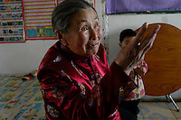 Meng Shujing (82) with great- grandson at home in Sanjiazi near the town of Qiqihar in Heilongjiang province in North-east China photographed on March 3rd 2007. She is explaining that only two other old ladies who can speak manchu like her remain in the village..She is among the last Manchu speakers (less than 100 in the world).