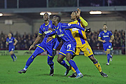 Tom Elliott of AFC Wimbledon, Ade Azeez of AFC Wimbledon stop Kristin Pearce of Mansfield Town during the Sky Bet League 2 match between AFC Wimbledon and Mansfield Town at the Cherry Red Records Stadium, Kingston, England on 16 January 2016. Photo by Stuart Butcher.