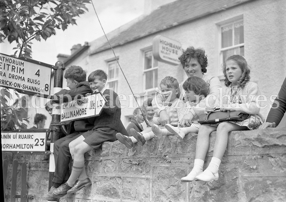 Watching the Tostal Parade, Drumshanbo Co. Leitrim. Children sitting on wall with roadsign post on left. June 7 1964.<br /> (Part of the Independent Ireland Newspapers/NLI Collection)