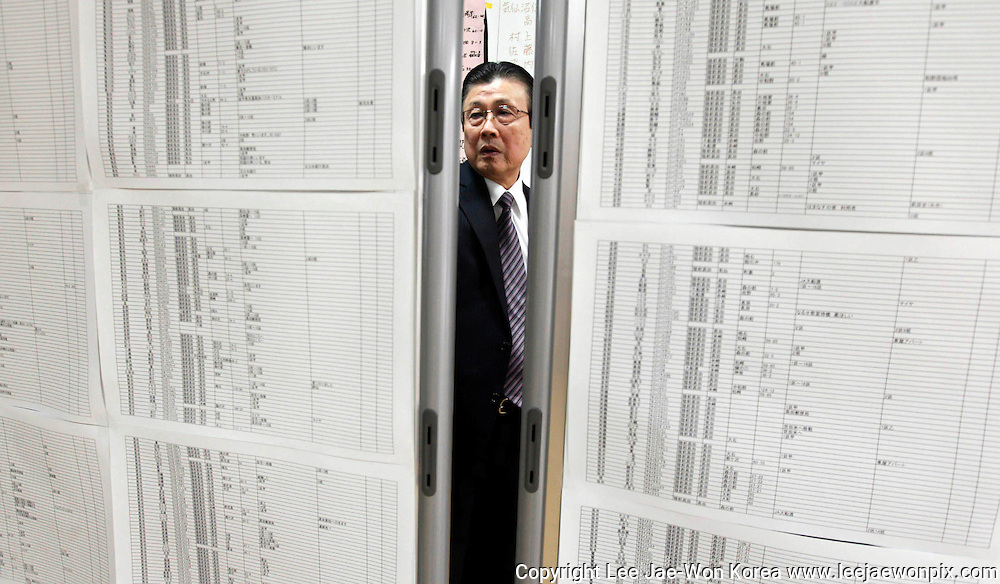 A man seeking for his relatives looks at a list of survivors at a shelter after an earthquake and tsunami in Rikuzentakata in Iwate prefecture, northeast Japan March 15, 2011. /Lee Jae-Won