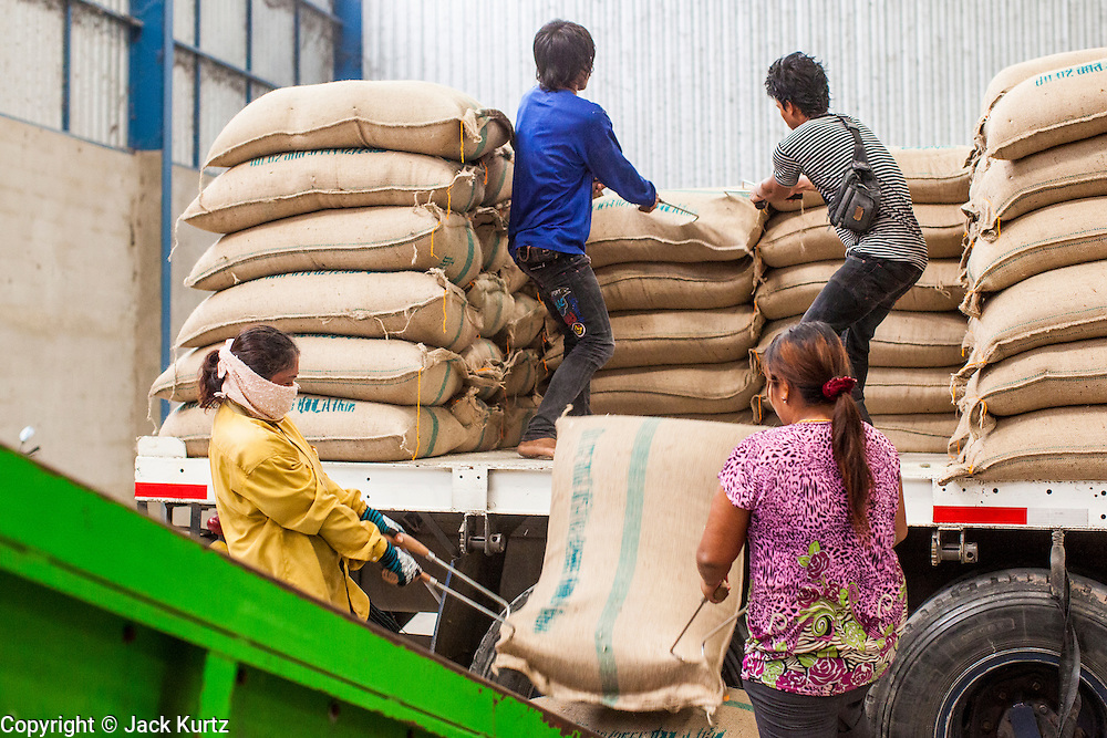 """15 NOVEMBER 2012 - PATHUM THANI, PATHUM THANI, THAILAND:  Workers unload trucks of rice bought from local farmers by the Thai government in a rice warehouse in Pathum Thani. The Thai government under Prime Minister Yingluck Shinawatra has launched an expansive price support """"scheme"""" for rice farmers. The government is buying rice from farmers and warehousing it until world rice prices increase. Rice farmers, the backbone of rural Thailand, like the plan, but exporters do not because they are afraid Thailand is losing its position as the world's #1 rice exporter to Vietnam, which has significantly improved the quality and quantity of its rice. India is also exporting more and more of its rice. The stockpiling of rice is also leading to a shortage of suitable warehouse space. The Prime Minister and her government face a censure debate and possible no confidence vote later this month that could end the scheme or bring down the government.   PHOTO BY JACK KURTZ"""