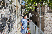 ACCIAROLI (POLLICA), ITALY - 5 OCTOBER 2016: 82-years old Fenisia La Greca is here on her balcony overlooking the harbor in Acciaroli, a hamlet in the municipality of Pollica, Italy, on October 5th 2016. Fenisia La Greca grows fruit and vegetables in her own garden.<br /> <br /> To understand how people can live longer throughout the world, researchers at University of California, San Diego School of Medicine have teamed up with colleagues at University of Rome La Sapienza to study a group of 300 citizens, all over 100 years old, living in Acciaroli (Pollica), a remote Italian village nestled between the ocean and mountains in Cilento, southern Italy.<br /> <br /> About 1-in-60 of the area's inhabitants are older than 90, according to the researchers. Such a concentration rivals that of other so-called blue zones, like Sardinia and Okinawa, which have unusually large percentages of very old people. In the 2010 census, about 1-in-163 Americans were 90 or older.