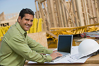 Construction worker using laptop, portrait