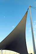 parasol in the form of a sail and sailing boats masts during sunset