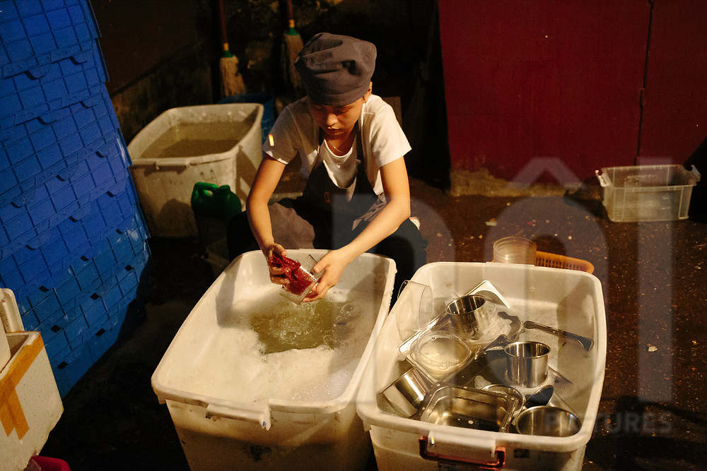 Worker doing the dishes in the backyard of a restaurant, Hanoi, Vietnam, Southeast Asia