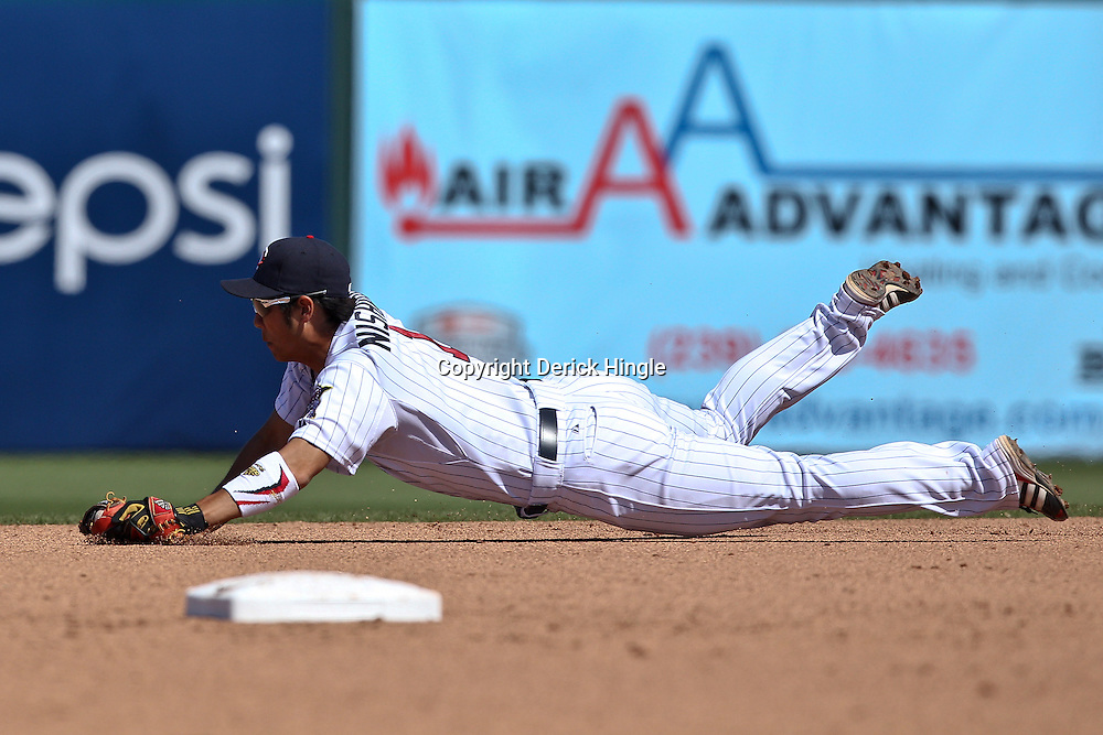 March 11, 2011; Fort Myers, FL, USA; Minnesota Twins second baseman Tsuyoshi Nishioka (1) dives to make a stop during a spring training exhibition game against the Boston Red Sox at Hammond Stadium.  Mandatory Credit: Derick E. Hingle-US PRESSWIRE