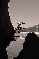 A boy is jumping into the water in a sea cave.  In the background is the ocean and the cliffs.