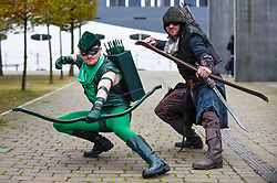 © Licensed to London News Pictures. 25/10/2019. LONDON, UK. Men dressed as (L to R) DC's Green Arrow and Pirate Green Arrow join other cosplayers from all over the world attending the opening day of the bi-annual MCM Comic Con event at the Excel Centre in Docklands.  The event celebrates popular culture such as video, games, manga and anime providing many attendees with the opportunity to dress up as their favourite characters.  Photo credit: Stephen Chung/LNP