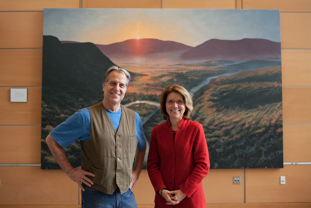 Mass College of Liberal Arts president Mary Grant (R) and internationally known artist Steve Hannock, stand in front of Hannock's painting that hangs in the atrium of the Feigenbaum Center for Science and Innovation, in North Adams on Thursday, October 10, 2013. The long-struggling mill town of North Adams has been revitalized by an infusion of art and artists, encouraged by the state college there and city itself. As a result, hundreds of artists now call it home.  (Matthew Cavanaugh)