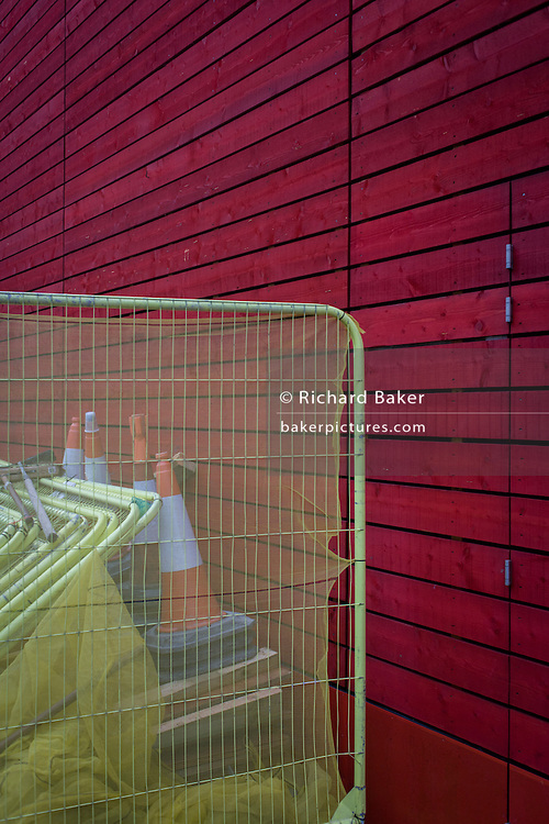 Yellow fencing and red wall of  the 250-seat wood panelled auditorium for the National Theatre (NT) designed by architect Haworth Tompkins, entitled The Shed on London's Southbank. The Shed is a temporary venue for the National Theatre on London's South Bank. Conceived by Haworth Tompkins and theatre consultants Charcoalblue, it was then designed and built in little more than a year.