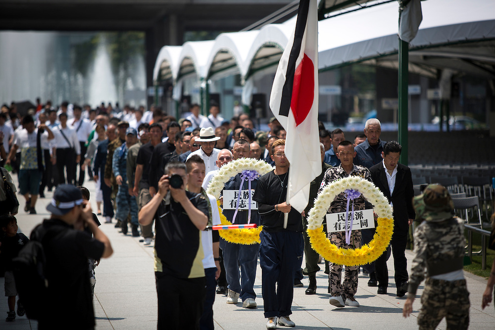 """HIROSHIMA, JAPAN - AUGUST 5 : A group of Japanese nationalists and militarists lays wreath and paid their respects to the victims of the Hiroshima bombing in front of the cenotaph ahead of the 71st anniversary of the atomic bombing on Hiroshima at Hiroshima Peace Memorial Park in Hiroshima, western Japan, Friday, August 5, 2016. Japan marked the 71st anniversary of the atomic bombing on Hiroshima. On August 6, 1945, during World War II, the United States dropped a uranium gun-type atomic bomb named """"Little Boy"""" on the city of Hiroshima which instantly killed an estimated 80,000 people, tens of thousands more would later die of radiation exposure. Three days later, a second American B-29 bomber dropped a plutonium implosion-type bomb """"Fat Man"""" on Nagasaki, killing an estimated 40,000 people. (Photo: Richard Atrero de Guzman/NURPhoto)"""