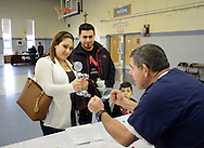 From left, Jackie Torres of Burlington, New Jersey tests her hand strength while Lower Bucks Hospital's Jay Witkowski cheers her on and Jose Torres and Steve Torres, 7 watch during a Health Fair sponsored by Lower Bucks Hospital  and held at St. Mark's School Hall Sunday March 13, 2016 in Bristol, Pennsylvania. (Photo by William Thomas Cain)