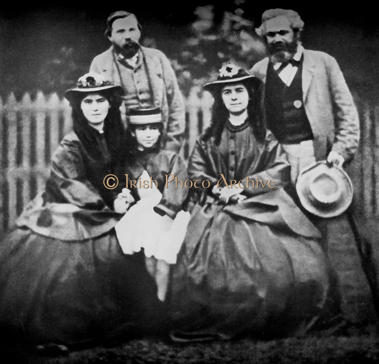 Karl Marx with his daughters Jenny, Lara and Eleanor standing behind (right), is Freidrich Engels