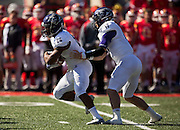 John David Baker (17) hands off the ball to Charcandrick West (17) of the Abilene Christian Wildcats during Saturday's football game against the Pittsburg State Gorillas at Carnie Smith Stadium on October 5, 2013 in Pittsburg, Kansas. (David Welker)