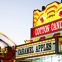 Photo of amusement park ride and concession stand food sign with cotton candy and caramel apples.  Photo is high resolution.