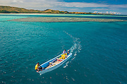 Little boat in the blue lagoon, Yasawas, Fiji, South Pacific