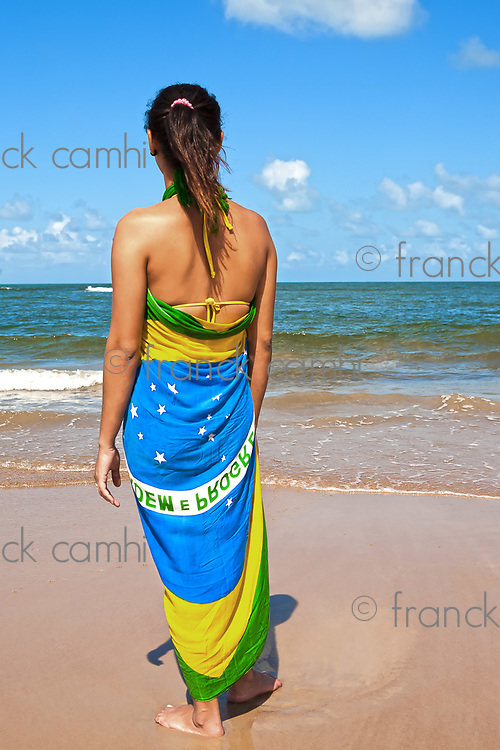 woman with the brazilian flag sarong on the beach looking at the sea