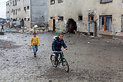 A boy is riding his bicycle in front of a decrepit building at the Roma settlement in Moldava nad Bodvou (2015). From about 800 inhabitants of the segregated settlement 'Budulovska Street' are roughly 392 children up to the age of 16 years (2014) .