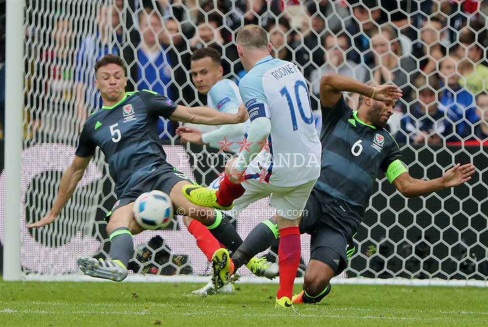 LENS, FRANCE - Thursday, June 16, 2016: Wales' James Chester and captain Ashley Williams block a shot from England's captain Wayne Rooney during the UEFA Euro 2016 Championship Group B match at the Stade Bollaert-Delelis. (Pic by David Rawcliffe/Propaganda)