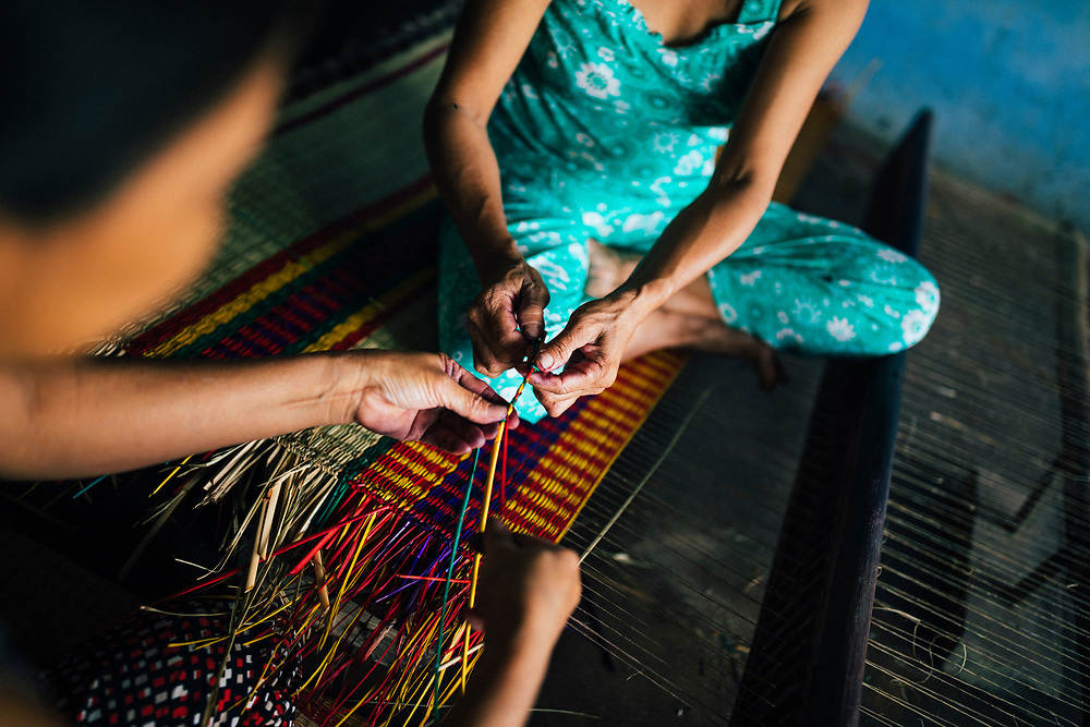 A woman weaves bamboo rugs in a small rural village in central Vietnam.
