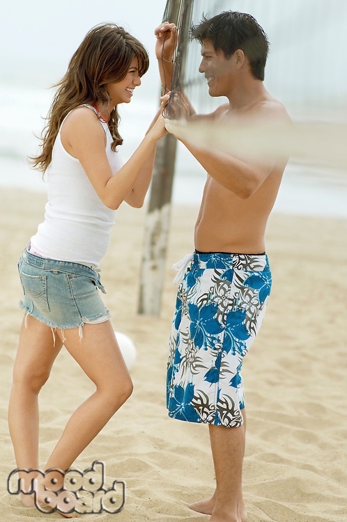 Couple on Beach Talking with Volleyball Net between Them