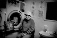 Homeless on streets / Streets like a nursing home:  Homeless elderly man harbors against a clothes drier for heat on a rainy winter day, Minowa, Tokyo, Japan.