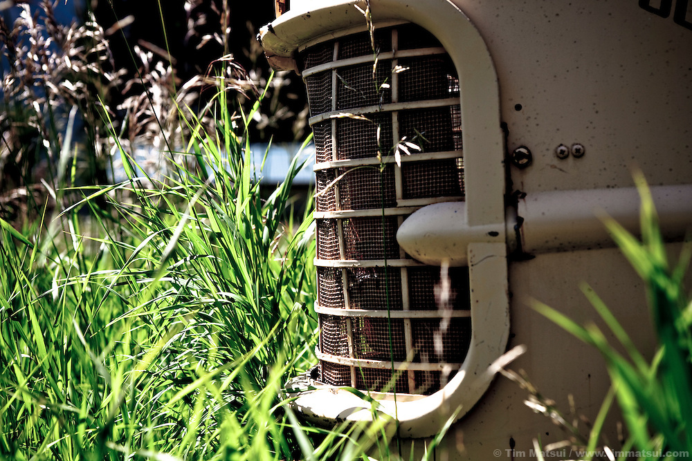 A closeup of the front grill of an old tractor in a field overgrown with tall grass.