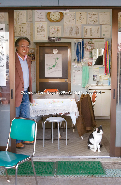 Nov. 27, 2009, Sakai City, Japan: This is Yuji Fukuya, age 50, a former plant manager from Hokkaido who came to the Tojinbo cliffs in Fukui Prefecture with the intent of committing suicide, but was instead saved by Yukio Shige. He is seen here at Shige's cafe on Nov. 27, 2009. As for Mr. Shige, the man who turned his life around, he is a 65 y/o retired policeman from Fukui Prefecture who founded the NPO Kokoro ni Hibiku Bunshu Henshukyoku in order to prevent suicides along the rocky cliffs at Tojinbo. Shige helped Fukuya get back on his feet and Fukuya currently shares as apartment with two other rescuees saved by Shige. Additionally, Mr. Fukuya works with Shige's NPO to help prevent other suicides at Tojinbo. This scenic tourist spot located on the Japan Sea coast in Sakai City, Fukui Prefecture has become a popular suicide spot, with twenty suicides occurring here in 2008 according to city officials. Shige took up his cause in 2004, just before retirement as a police deputy at a nearby police station where he was posted. When he discovered how many suicides were occurring here, he began patrolling the cliffs of Tojinbo in order to spot those contemplating suicide. Shige soon began easily spotting distressed individuals and would talk to them out of their attempts to end their lives. Upon retirement he opened a small cafe at Tojinbo where he also set up his NPO. Since then other volunteers have joined his cause and as of November 2009, Shige explains that he and his group have talked 222 out of committing suicide. They do this by patrolling the cliffs daily with binoculars in hand, and when they spot someone they kindly approach them and coax them away to Shige's cafe where they offer them tea and rice cakes. He also sees them safely home, and in cases where an individual is homeless, he finds them accommodations. However there are still some that slip past his watchful eyes as so far in 2009 thirteen people have jumped to their deaths here. Japan has one of