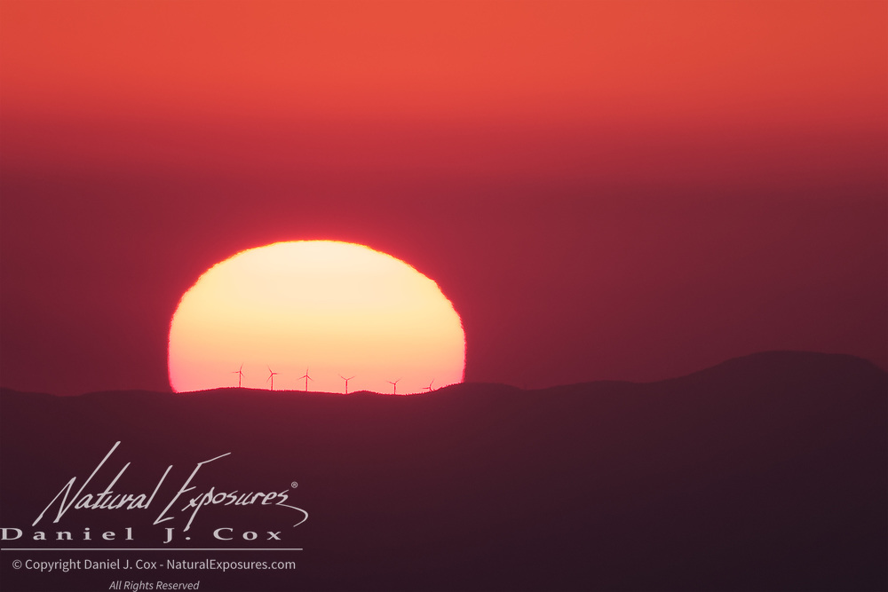 Looking down from Sommet du Ventoux, the sun begins to set below the horizon with a thick layer of dust and smog creating a beautiful red orb. Wind turbines are silhouetted against the sun. France