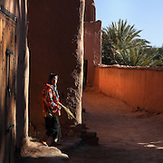 Girl coming out in the morning with sweeping brush at Ksar Ait Ben Haddou, earthen fortified city, Ounila valley, Ouarzazate province, Morocco. The ksar is a group of earthen houses surrounded by high defensive walls with corner towers, in traditional pre-Saharan style.  The village stands above the Oued Marghen river in the High Atlas and was a stop on the caravan route from the Sahara to Marrakech. It was founded in the 17th century and has been a UNESCO World Heritage Site since 1987. Picture by Manuel Cohen