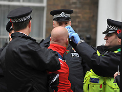 © Licensed to London News Pictures. 11/11/2011. London, UK. A man receives first aid treatment and is handcuffed by police officers.  Police arrest members of the EDL near the Cenotaph following a Remembrance Day service today (11/11/2011). A large group of EDL members where arrested. Police a. Photo credit : Stephen Simpson/LNP