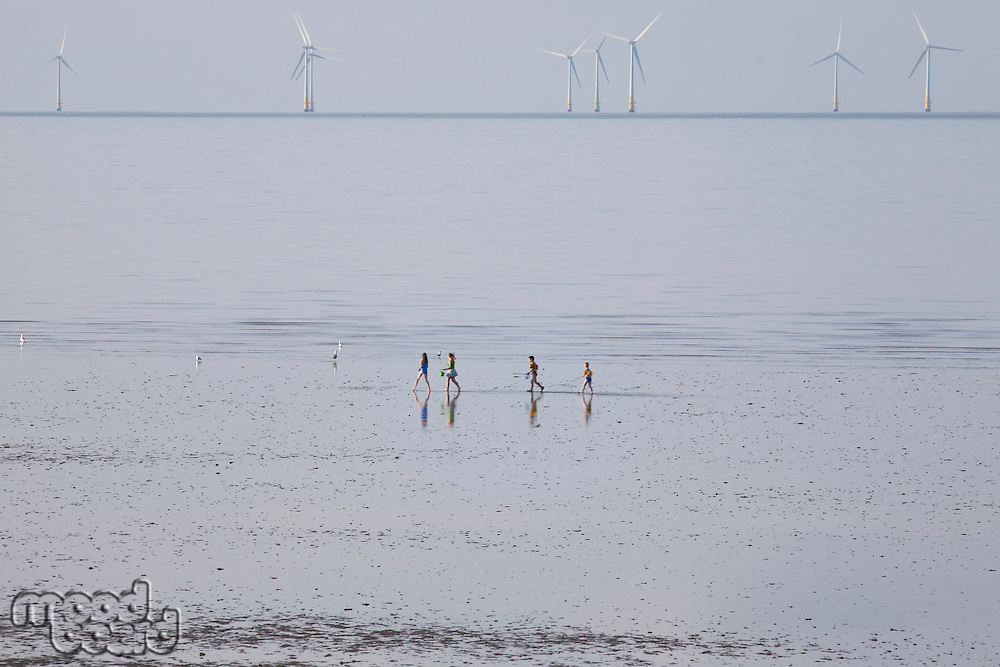 People running on beach wind farm in distance