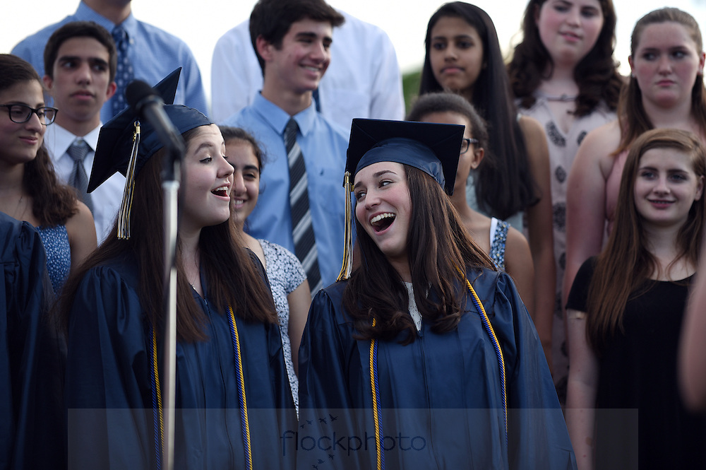 Seniors Katie Mullen (l) and Adina Jacobson sing with the Needham High School Chorus during the school's graduation ceremony, Monday, June 6, 2016.<br /> Wicked Local staff photo / Kate Flock
