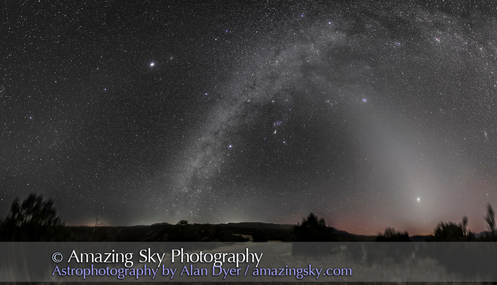 A 160&deg; panorama showing: <br /> - the Zodiacal Light (at right in the west)<br /> - the Milky Way (up from the centre, in the south, to the upper right)<br /> - the Zodiacal Band (faintly visible running across the frame at top)<br /> - the Gegenschein (a brightening of the Zodiacal Band at left of frame in the east in Leo)<br /> <br /> Along the Milky Way are dark lanes of interstellar dust, aprticularly in Taurus above and to the right of Orion. Red nebulas of glowing gas also lie along the Milky Way, such as Barnard&rsquo;s Loop around Orion.<br /> <br /> The Zodiacal Light, Band and Gegenschein all lie along the ecliptic, as do Mars, Venus and Jupiter shown here. <br /> <br /> Orion is at centre, in the south, with Canis Major and the bright star Sirius below and to the left of Orion. Canopus is just setting on the southern horizon at centre. <br /> <br /> To the right of Orion is Taurus and the Pleiader star cluster at the top of the Zodiacal Light pyramid. <br /> <br /> Venus is the bright object in the Zodiacal Light at right, in the west, while fainter Mars is below Venus. <br /> <br /> At far right at the frame edge, in the northwest, is the Andromeda Galaxy, M31. <br /> <br /> Jupiter is the bright object at upper left, in the east, in the Zodiacal Band, and near the Beehive star cluster. <br /> <br /> The Zodiacal Light, Band and Gegenschein are caused by sunlight reflecting off cometary and meteoric dust in the inner solar system. The Gegenschein, or &ldquo;counterglow,&rdquo; can be seen with the naked eye but is a subtle and diffuse brightening of the sky in the spot opposite the Sun. It is caused by sunlight reflecting directly back from comet dust, with the effect greatest at the point opposite the Sun. <br /> <br /> Glows like the Zodiacal Light require reasonably dark skies, but the fainter Zodiacal Band and Gegenschein require very dark skies.<br /> <br /> Glows on the horizon are from distant SIlver City, Las Cruces and El Paso. The brighter sky at right is from the last vestiges of evening twilight. Some green and red airglow bands also permeate the sky.<br /> <br /> I shot this March 10, 2015 from the summit