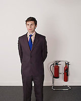 Businessman standing near fire extinguisher