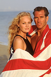 beautiful All American couple wrapped in an American Flag on the beach