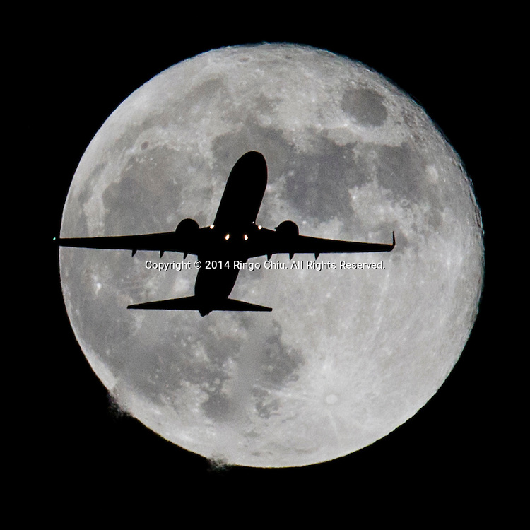 An airplane approaches Los Angeles International Airport and flies past the full moon on Wednesday, October 8, 2014 in Los Angeles, California. (Photo by Ringo Chiu/PHOTOFORMULA.com)