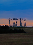 Photograph of windmilss on a ranch in western Nebraska, sunset.