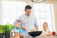 Children looking at father preparing food in kitchen