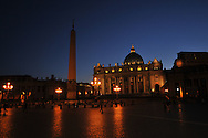 The sun sets at St. Peter's Square at the Vatican in Rome, Italy with St. Peter's Basilica and the Vatican.