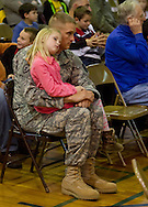 Westfall, Pennsylvania - A Delaware Valley  Elementary School student sits on her father's lap at an assembly in the gymnasium where veterans were honored on Nov. 8, 2013.