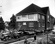 House movers lead this four-unit brick apartment building on oak rollers on 18-by-20-inch beams along East 43rd Street from Pasadena Place to a new site at Eighth Avenue Northeast and East (now Northeast) 43rd Street on Aug. 28, 1958. (Seattle Times archive)