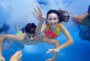 Teenage boys and girls swimming underwater at home pool